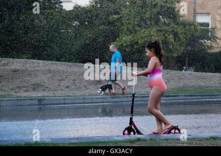 London, UK. 14th Sep, 2016. A girl riding a scooter cools off in a fountain in London, England on Sept. 14, 2016, - Stock Photo