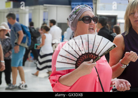 London UK. 15th September 2016.  A woman cools off with a fan at Waterloo station from the Indian summer heat as - Stock Photo