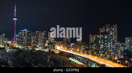 Glowing cityscape and buildings as light streaks along Gardiner Expressway on a hot & muggy summer night in Lakeside - Stock Photo
