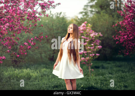 Beautiful blonde girl in pink peach and sakura garden.  Female outdoors spring portrait, young woman with  at green - Stock Photo