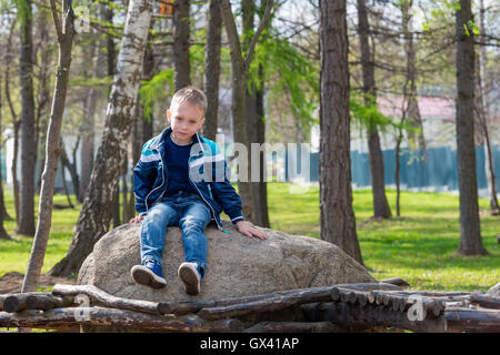The boy takes a break from the games sitting on the stone - Stock Photo