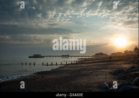 A beautiful sunset over the beach, sea and Worthing Pier in Worthing, West Sussex, England. - Stock Photo