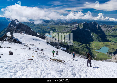 Hikers on the snow descending from Titlis mountain summit to the Titlis cable car station. Engelberg, Switzerland. - Stock Photo