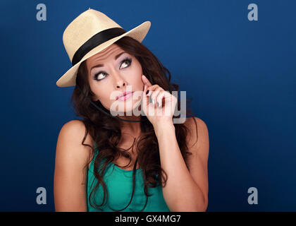 Fun grimacing frightened woman in hat thinking and looking up on empty space background. Curly brown long hair style. - Stock Photo