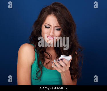 Cranky surprising grimacing young woman reading sms on mobile phone holding it in hand on blue background - Stock Photo