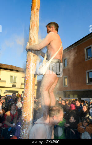 Tesserete, Switzerland - 13 February 2016: men trying to climb the greasy pole of the carnival at Tesserete on the - Stock Photo