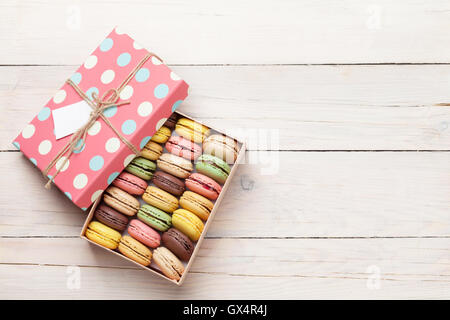 Colorful macaroons on wooden table. Sweet macarons in gift box. Top view with copy space for your text - Stock Photo