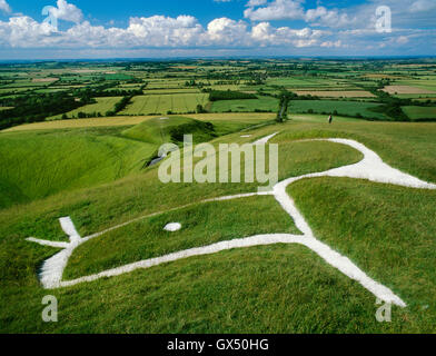 A walker pauses to admire the view from beside the Uffington White Horse hill figure above the flat-topped mound - Stock Photo