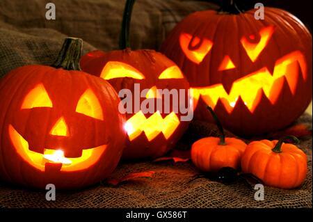 Group of spooky Halloween Jack o Lanterns lit at night - Stock Photo