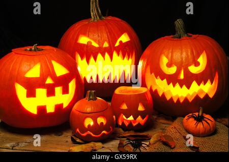 Halloween night scene with a group of spooky illuminated Jack o Lanterns - Stock Photo
