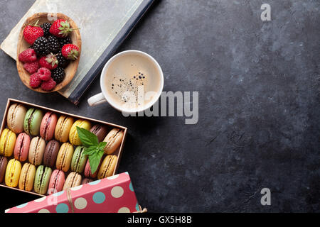 Colorful macaroons and berries on stone table. Sweet macarons and coffee cup. Top view with copy space - Stock Photo