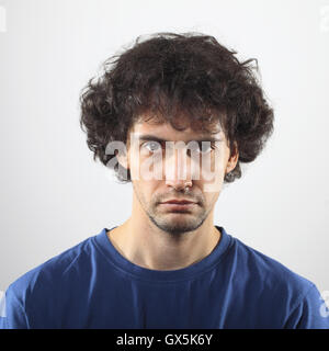 Sad handsome young man portrait in blue shirt looking at camera. - Stock Photo