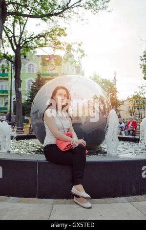 Young cute brunette girl sitting on bench against globe monument in the city - Stock Photo