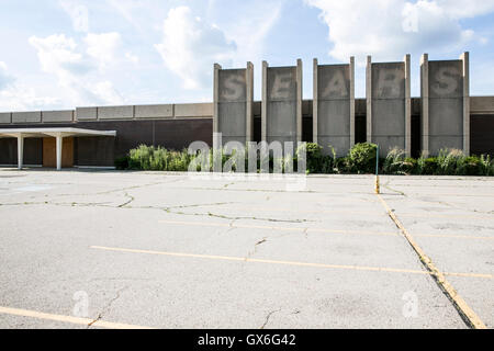 The outline of a logo sign outside of an abandoned Sears retail store in Trotwood, Ohio on July 23, 2016. - Stock Photo