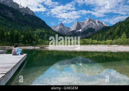 View of the Julian Alps from Kranjska Gora with Jasna Lake and girl sitting on pier in Slovenia - Stock Photo