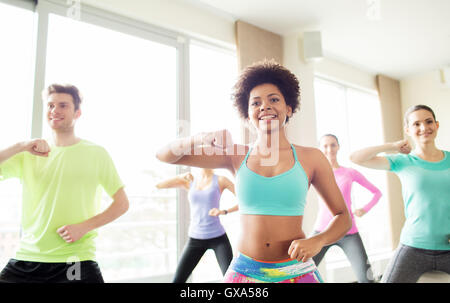 group of happy people exercising or dancing in gym - Stock Photo