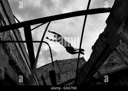 A Colombian parkour runner jumps over a gap inside an abandoned house during free running trainings in Bogotá, Colombia. - Stock Photo