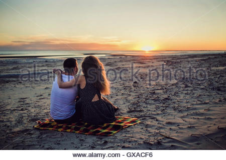 Couple sitting near the sea on sunset - Stock Photo