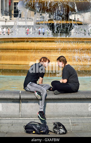 London, England, UK. Trafalgar Square - young people sitting on one of the fountains. - Stock Photo