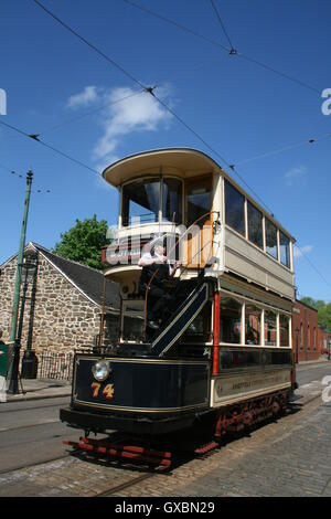 A conductor climbs the stairs of Tram 74 formerly belonging to Sheffield Corporation Tramways, now at Crich Tramway - Stock Photo