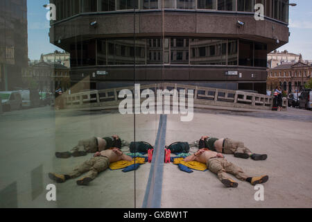 Two men sleep on the ground near Pudding lane, the location of the Great Fire of London (1666), on 13th September - Stock Photo