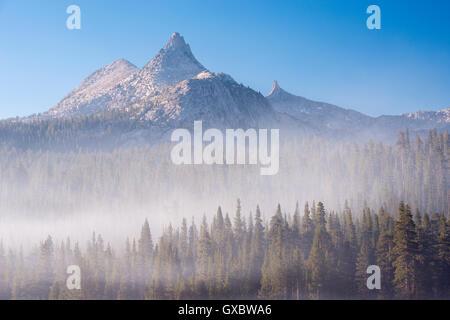 Unicorn Peak rising above a mist shrouded forest, Yosemite National Park, California, USA. Autumn (October) 2014. - Stock Photo
