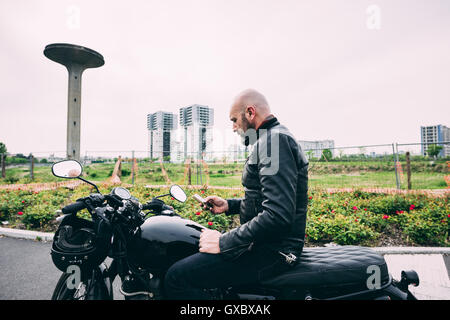 Mature male motorcyclist sitting on motorcycle reading smartphone text - Stock Photo