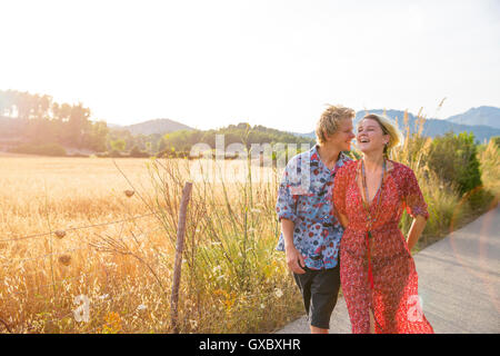 Young couple laughing whilst strolling along rural road, Majorca, Spain - Stock Photo
