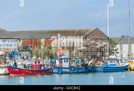 Several small fishing boats moored on a river in the UK. - Stock Photo