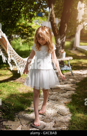 Little girl walking on the stones in the garden and having fun outdoor. - Stock Photo