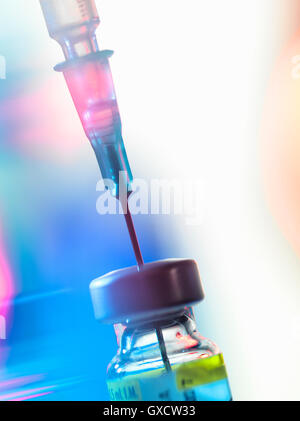 Syringe inserted into a vaccine vial - Stock Photo