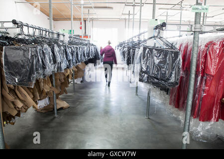 Woman between clothes rail in sewing factory sample room - Stock Photo