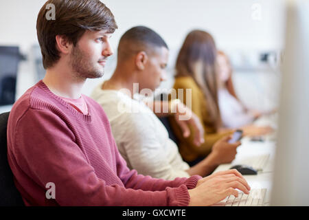 Students typing on computers in higher education college computer room - Stock Photo