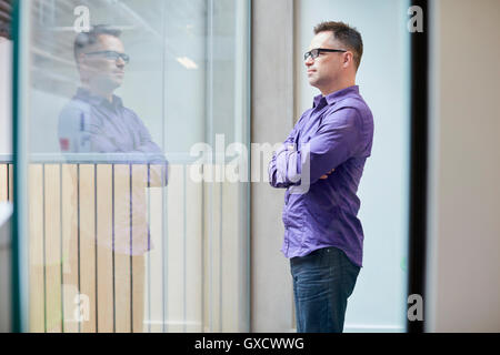 Male designer looking out from window in design studio - Stock Photo