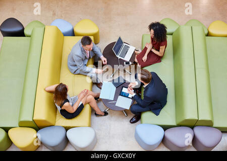 Overhead view of businessmen and businesswomen meeting on design studio sofas - Stock Photo