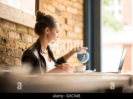 Young businesswoman pouring tea in cafe - Stock Photo