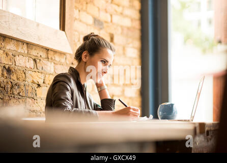 Young businesswoman making notes in cafe - Stock Photo