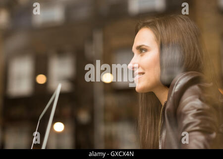 Window view of young businesswoman with laptop in cafe - Stock Photo