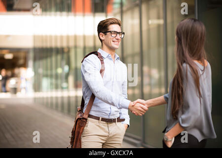 Businessman and woman shaking hands outside office, London, UK - Stock Photo