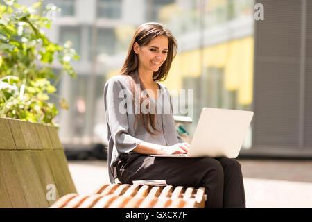 Businesswoman typing on laptop on park bench, London, UK - Stock Photo