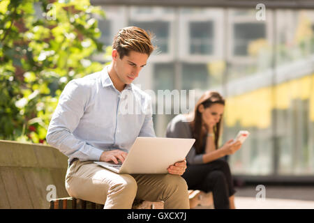 Businessman typing on laptop in city, London, UK - Stock Photo