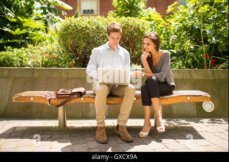 Young businesswoman and man using laptop on bench, London, UK - Stock Photo