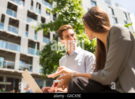 Young businesswoman and man using laptop and chatting, London, UK - Stock Photo