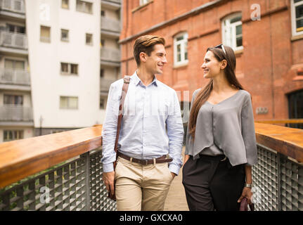 Young businesswoman and man chatting on footbridge, London, UK - Stock Photo