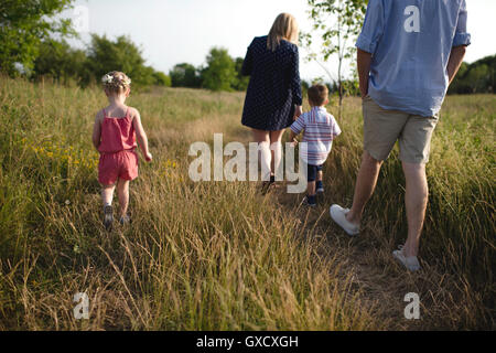 Rear view of mid adult parents strolling in meadow boy and girl - Stock Photo
