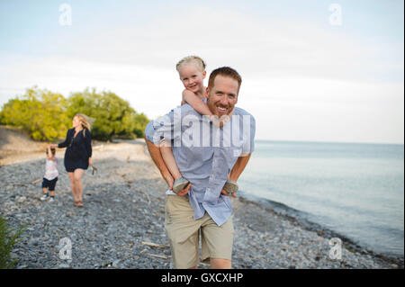 Father giving daughter a piggy back at Lake Ontario, Oshawa, Canada - Stock Photo
