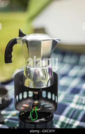 Stovetop espresso maker on camping stove, Fondo, Trentino, Italy - Stock Photo