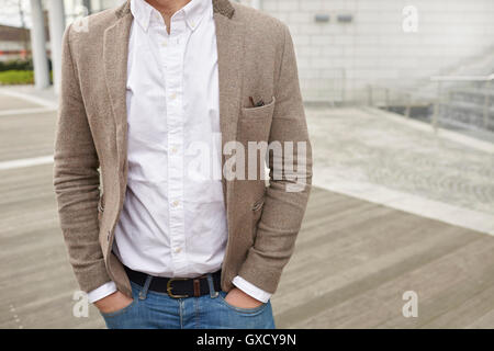 Mid section of businessman with hands in pockets - Stock Photo