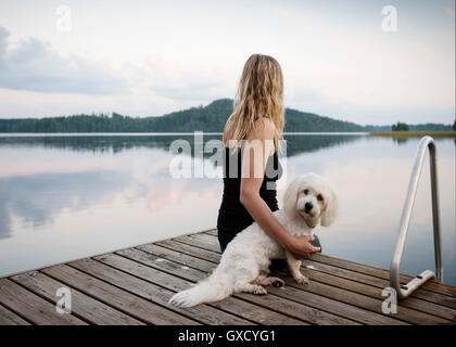 Woman with coton de tulear dog looking out from lake pier, Orivesi, Finland - Stock Photo