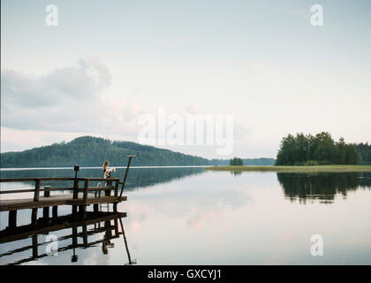 Woman and coton de tulear dog looking out from lake pier, Orivesi, Finland - Stock Photo
